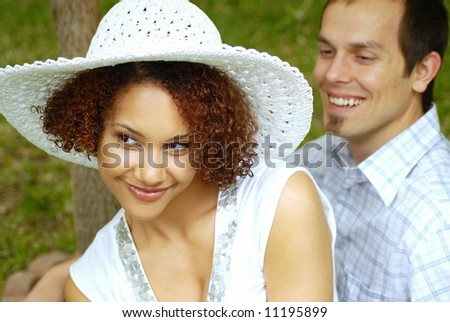 Two young lovers sitting together and flirting at the park - stock photo