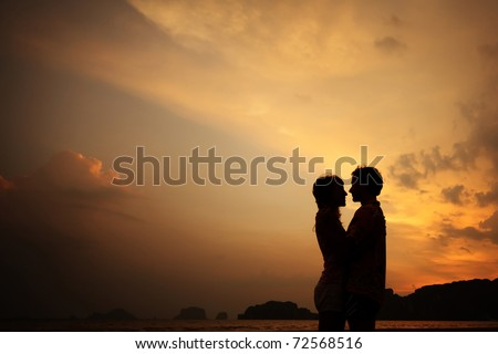 Two young lovers standing on a beach and looking to each other on sunset background