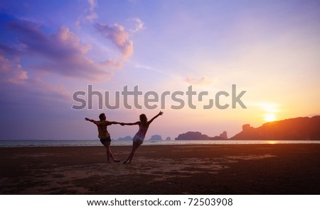 Two young lovers standing on beach and holding each other hands on sunset background