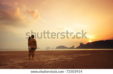 Two young lovers standing on beach and looking to a sun