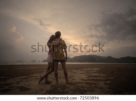 Two young lovers standing on beach and looking to a sunset sky - stock photo
