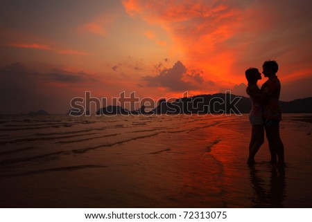 Two young lovers standing on wet beach and looking to each other on sunset background