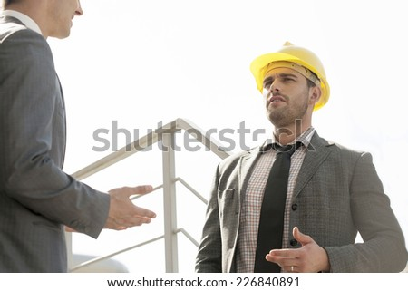 Two young male engineers discussing on stairway against clear sky - stock photo