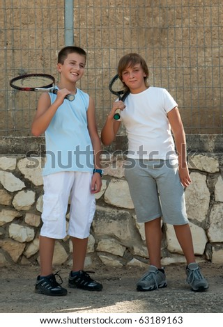 Two young male friends with rackets on tennis court smiling . - stock photo