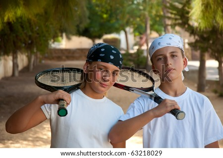 Two young male friends with rackets  smiling . - stock photo