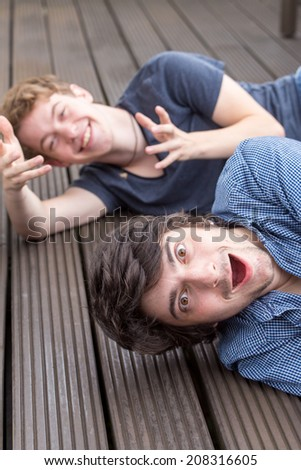 Two young male models are lying on the ground, laughing and having a lot of fun. The front model is very surprised while the one behind is doing a funny gesture and laughs - stock photo