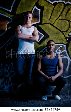 Two young male models on graffiti background with grungy look - stock photo