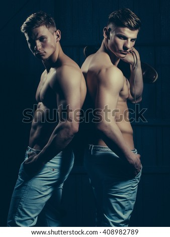 Two young male twins with sexy body showing their muscular torso and abs in studio - stock photo