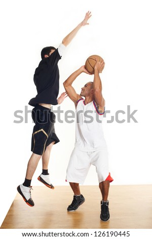 Two young man playing basketball - a mulatto and a white guy.