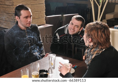 Two young mans and girl in a cafe