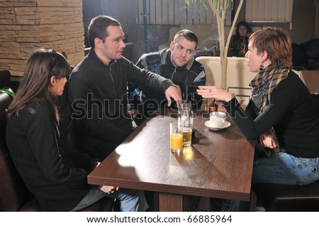Two young mans and two girls in a cafe