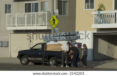 two young men and a women are packing household items to move