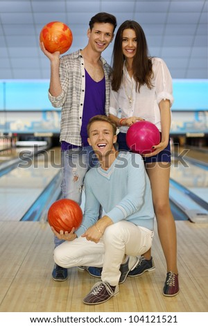Two young men and beautiful girl hold balls in bowling club; focus on sitting man; shallow depth of field; full body - stock photo