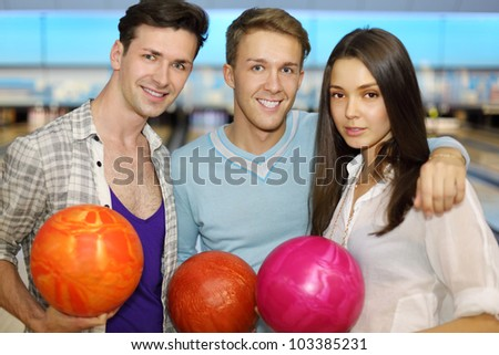 Two young men and beautiful girl hold bright balls in bowling club; focus on center man; shallow depth of field - stock photo