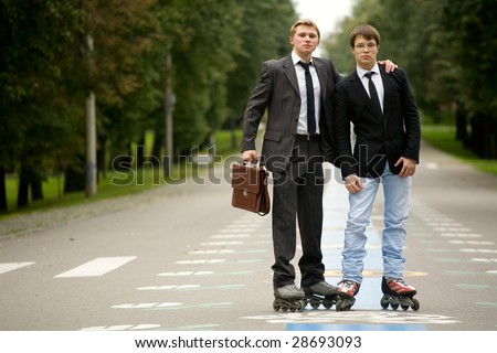 Two young men are standing on the road wearing rollerblades