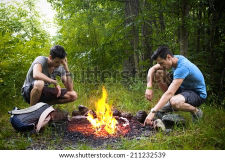 Two young men camping in the mountains crouching alongside a burning campfire with rucksack staring thoughtfully at the fire - stock photo