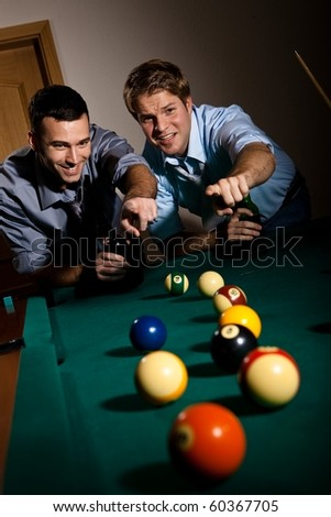 Two young men discussing snooker game, having beer, pointing at balls on table, smiling.? - stock photo