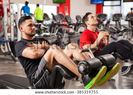 Two young men doing some crunches and working on their abs at the gym - stock photo