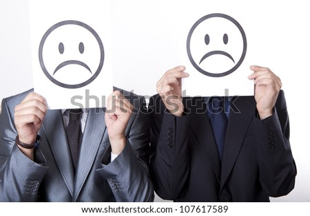 Two young men holding sad smiley faces. - stock photo