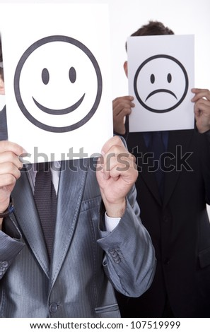 Two young men holding smiley and sad smiley face. - stock photo