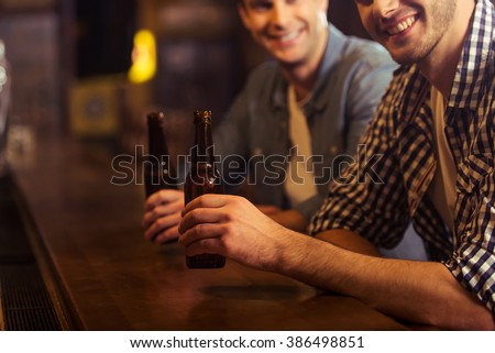 Two young men in casual clothes are smiling, looking at camera and holding bottles of beer while sitting at bar counter in pub, close-up - stock photo