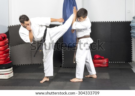 Two young men in kimono fighting during their training in the gym - stock photo