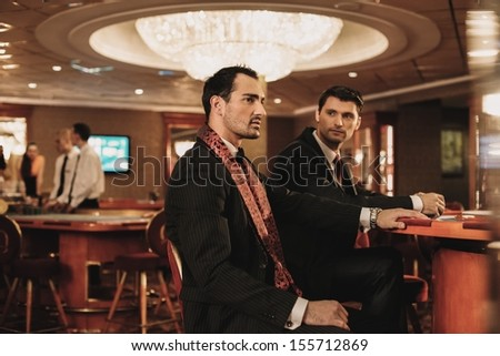 Two young men in suits behind table in a casino - stock photo