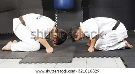 Two young men in white kimono down on their knees saluting in the gym - stock photo