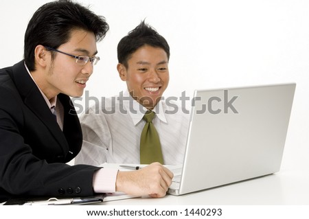 Two young men look happy with their work on a laptop (shallow depth of field)
