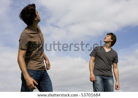 Two young men looking up to the sky - stock photo