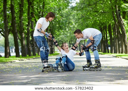 Two young men on roller lift a fallen girl - stock photo