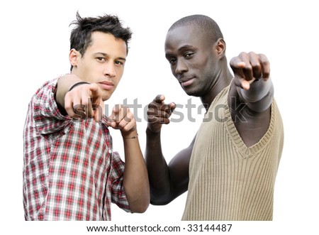 Two young men, one black and one Caucasian, pointing at the camera. - stock photo
