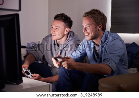 Two Young Men Playing Video Game At Home - stock photo