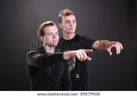 Two young men pointing fingers