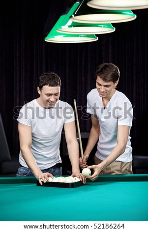 Two young men put spheres for billiards - stock photo