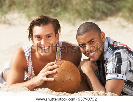 Two Young Men Relaxing On Beach With Football Together