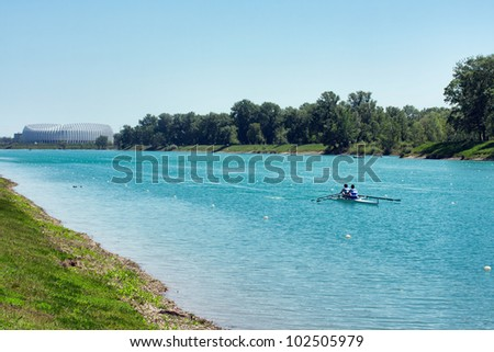 "Two young men rowing on lake ""Jarun"", arena Zagreb in back, Croatia - stock photo"