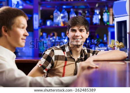 Two young men sitting at bar and talking - stock photo