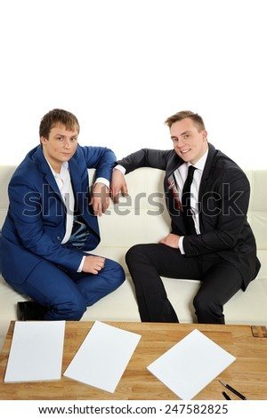 Two young men sitting on the couch. We are confident and relaxed, everything is in our hands.  Copy space above and magazine pages for your text.