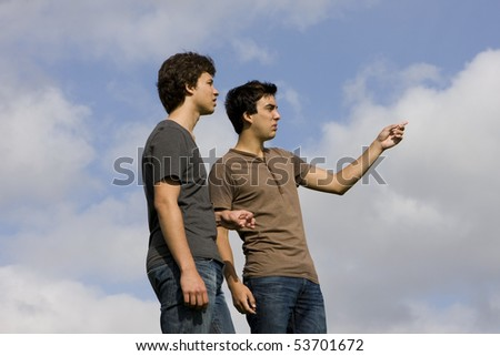 Two young men speaking and looking away - stock photo