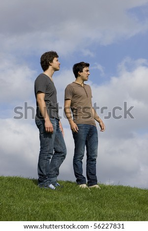 Two young men speaking and looking away