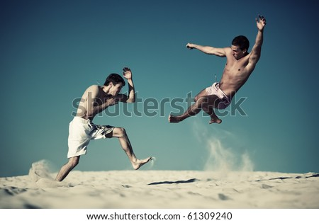 Two young men sport fighting on beach. Yellow and blue contrast colors. - stock photo