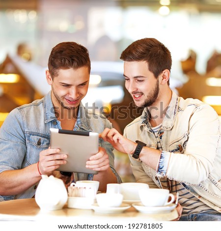Two young men / students using tablet computer in cafe  - stock photo