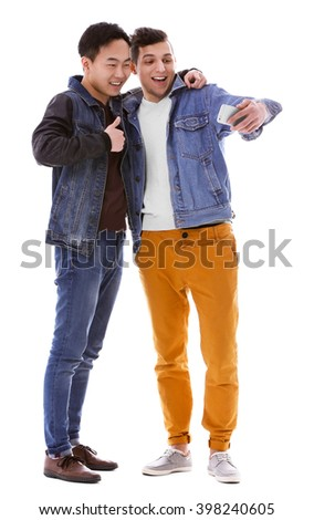 Two young men taking selfie with mobile phone isolated on white - stock photo