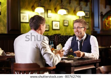 Two young men talking in the pub - stock photo