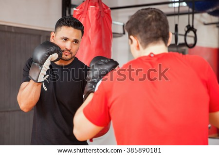 Two young men wearing boxing gloves and doing some sparring at the gym