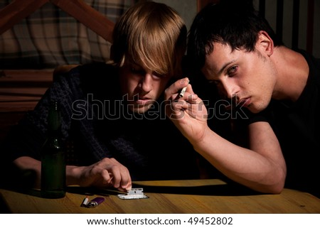 Two young men with heroin or cocaine on table - stock photo