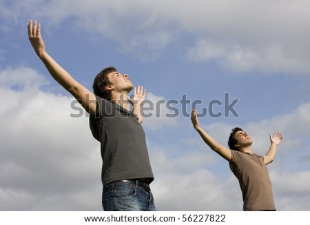 Two young men with there arms wide open enjoying life - stock photo