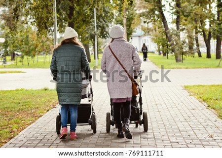 Two young moms girlfriends are walking with young children in strollers for an autumn Park. Women on a walk with the kids, the view from the back