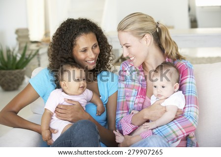 Two Young Mothers On Sofa At Home - stock photo